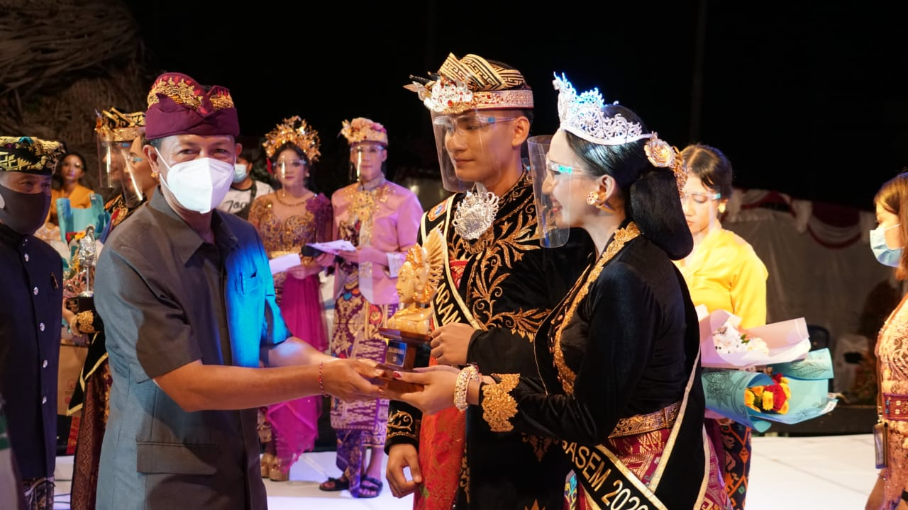 Pjs. Bupati Karangasem, I Wayan Serinah, menyerahkan piala pada Jegeg Bagus Karangasem saat menutup Karangasem Cultural Movement Carnival 2020, Jumat (31/10/2020) malam. Foto: ist