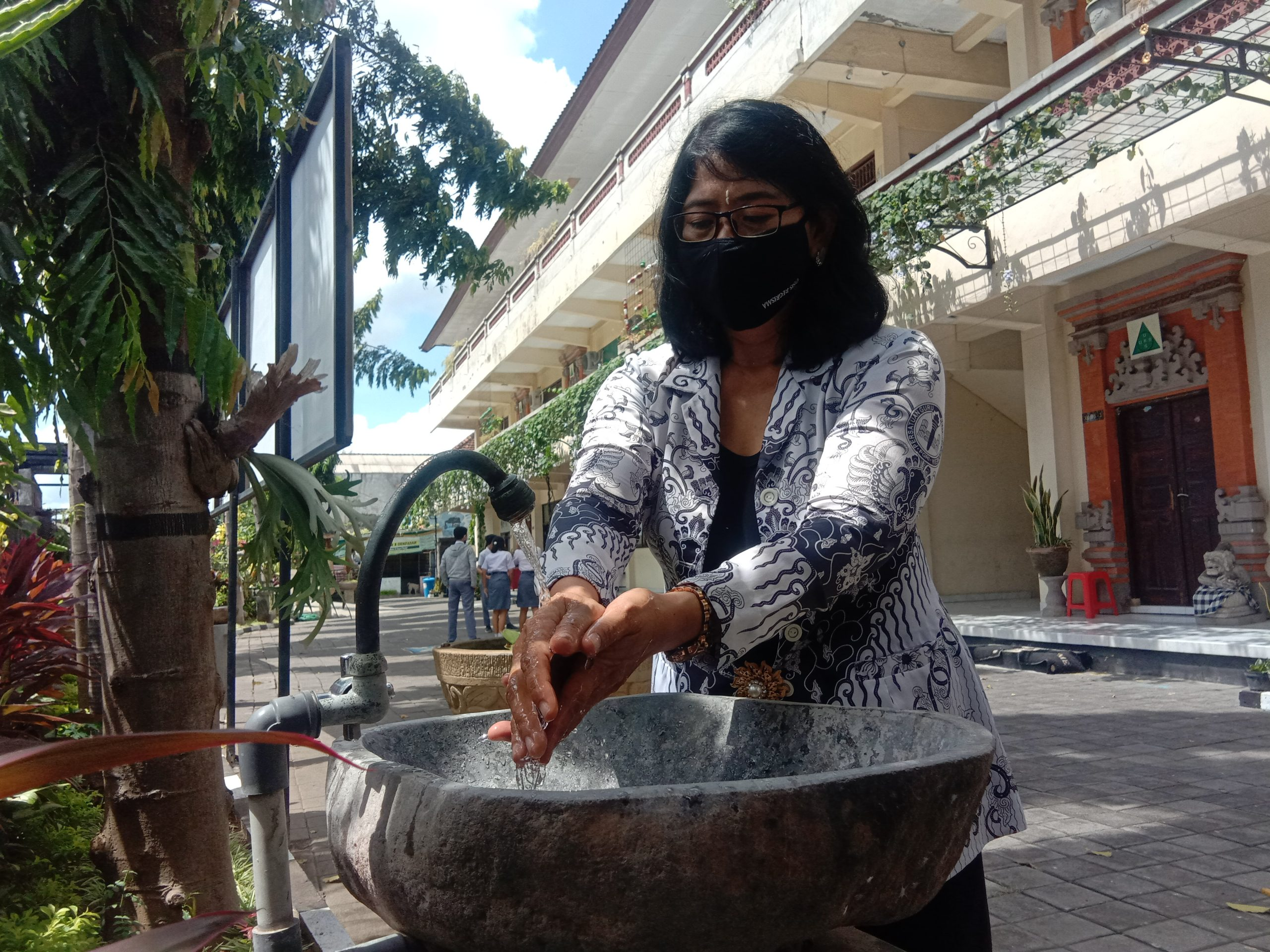 WAKASEK Humas SMA PGRI 2 Denpasar, AA Ayu Seriati tampak mencuci tangan dengan sabun dan membilasnya di air yang mengalir. Foto: alt