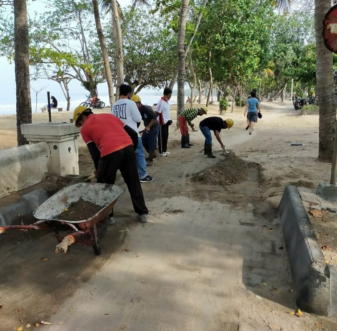 SEJUMLAH pekerja sedang merapikan pasir pada akses jalan setapak di Pantai Kuta. Foto: ist