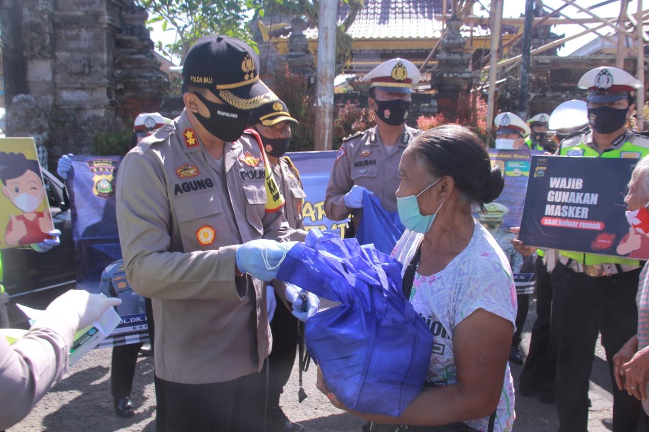 KAPOLRES Bangli, AKBP IGA Dhana Aryawan, membagikan paket sembako kepada warga usai Operasi Zebra Lempuyang di Jalan Merdeka, depan Pasar Kidul Bangli, Minggu (8/11/2020) pagi. Foto: gia
