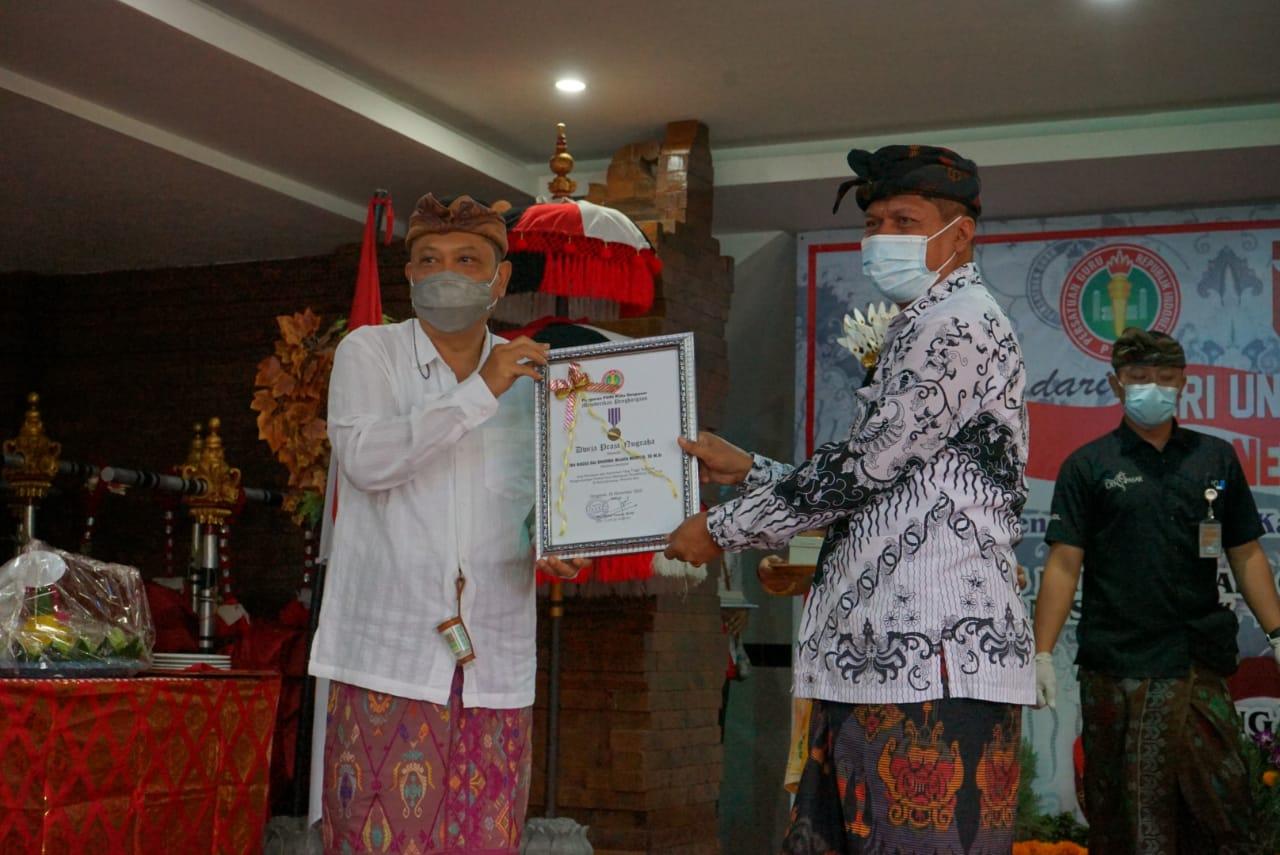 WALI Kota Denpasar, IB Rai Dharmawijaya Mantra menerima piagam penghargaan Dwija Praja Nugraha dari Ketua PGRI Kota Denpasar, I Ketut Suarya, Kamis (26/11/2020). Foto: tra