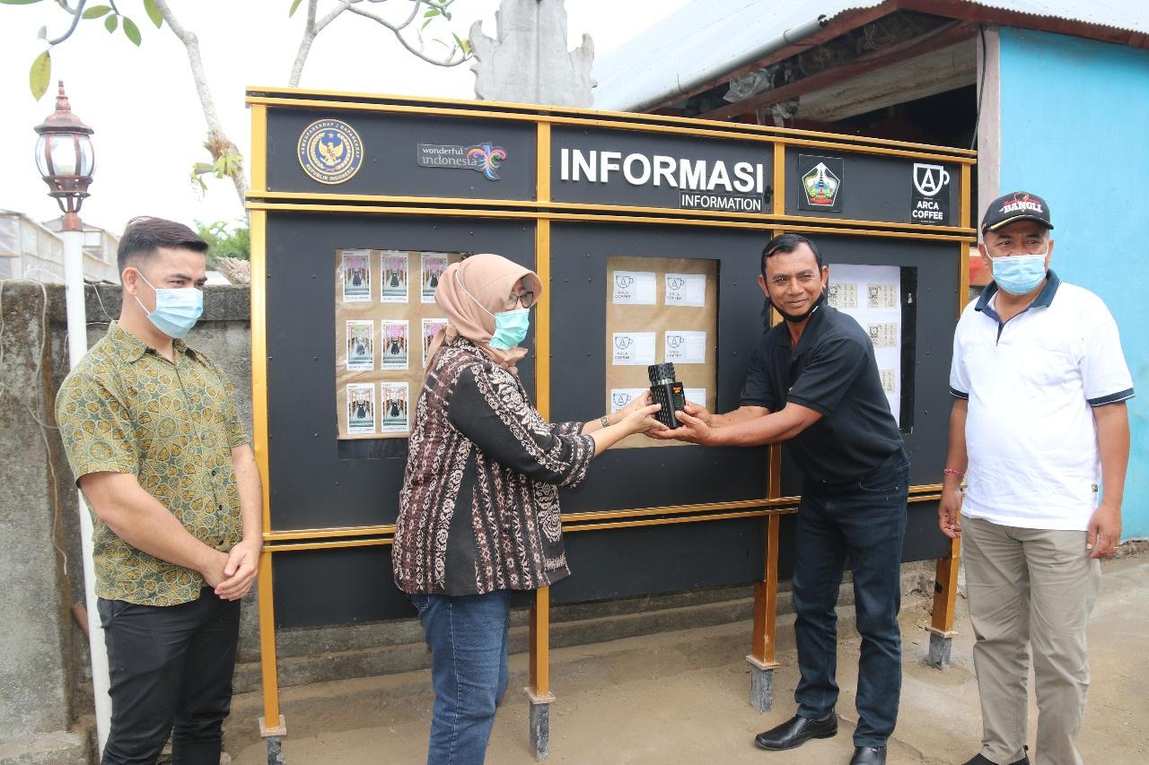 MIFTACHUL Farida menyerahkan alat pengolahan kopi dan diterima pengelola Arca Coffee di Desa Ulian, I Wayan Berana, didampingi Bupati Made Gianyar. Foto: gia