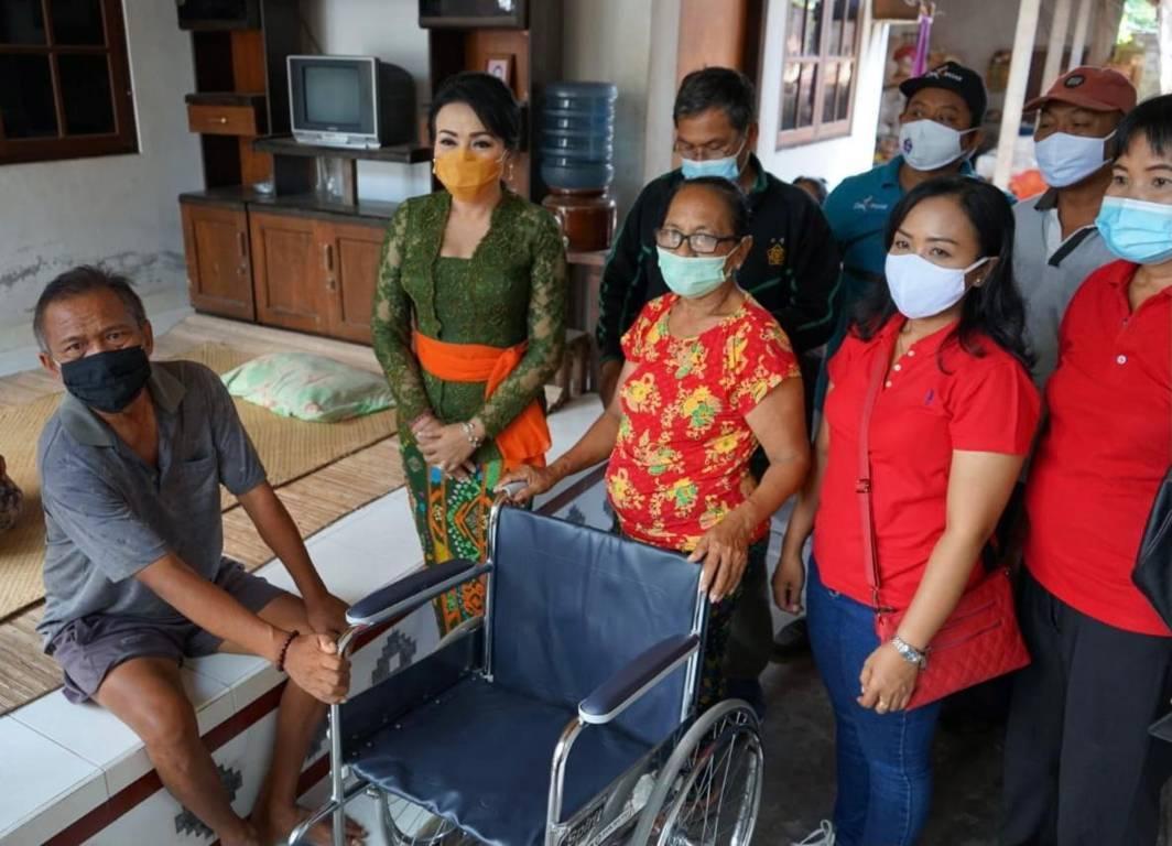 KETUA K3S Kota Denpasar, IA Selly Dharmawijaya Mantra, menyerahkan bantuan kursi roda kepada I Wayan Budra beralamat di Jalan Siulan Gang Dahlia No. 2 Kecamatan Denpasar Timur, Jumat (20/11/2020). Foto: ist