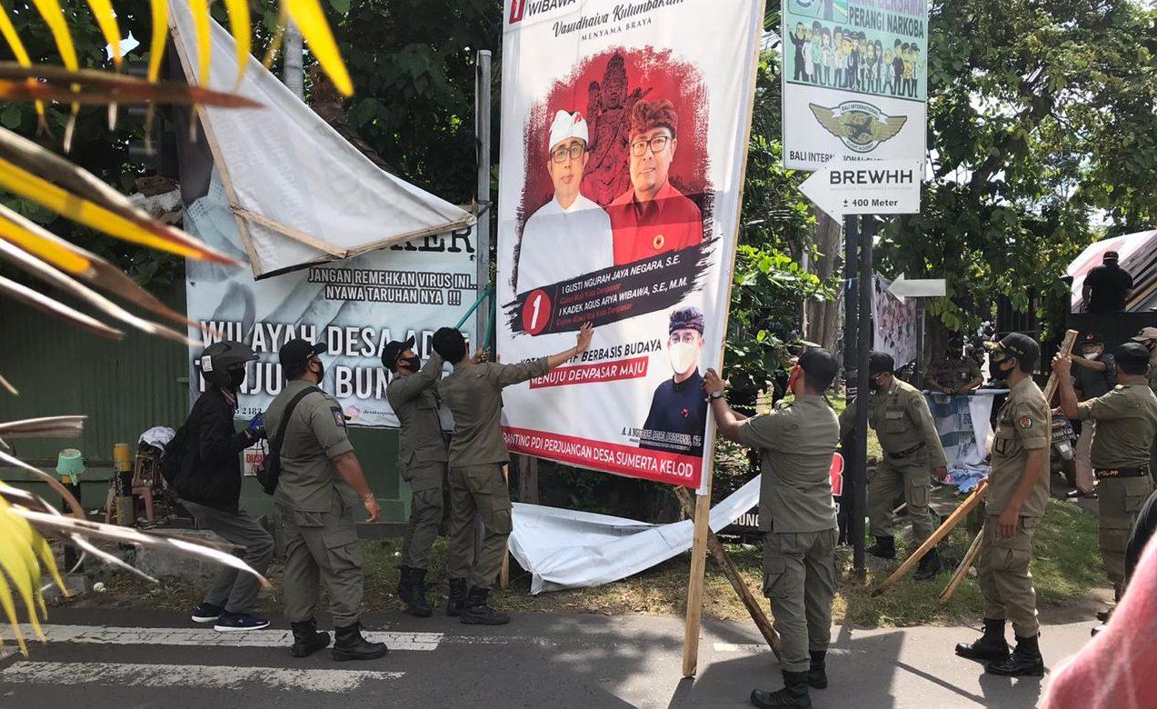SATPOL PP Denpasar menertibkan baliho liar paslon di luar yang difasilitasi KPU Denpasar di kawasan Renon, Denpasar, beberapa waktu lalu. Foto: Ist