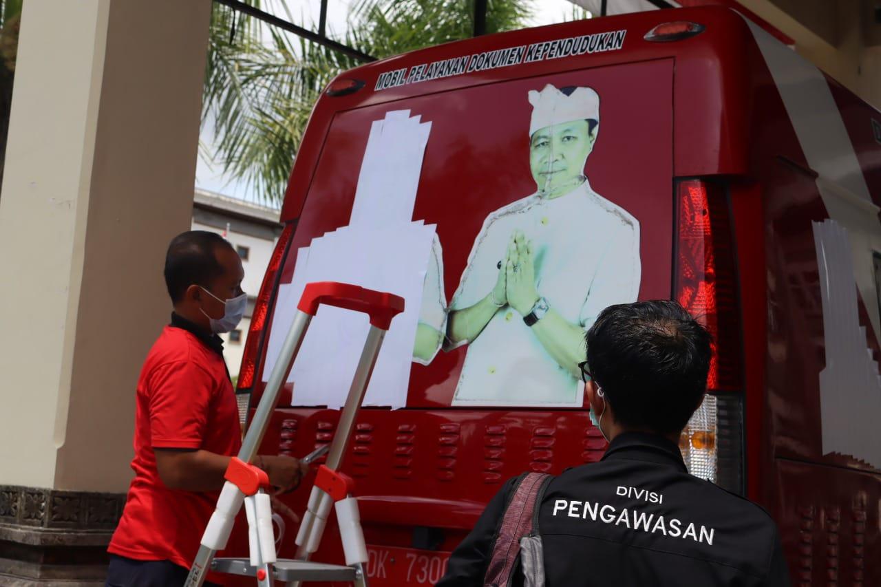 BAWASLU Badung bersama pegawai Pemkab Badung menutup foto paslon petahana yang dipasang di mobil operasional Pemkab Badung. Foto: Ist