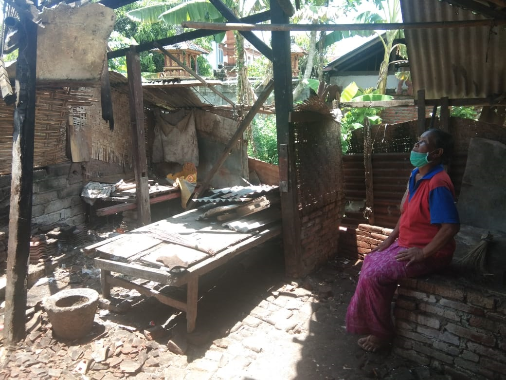 NI Komang Kari alias Jro Yasmin meratapi rumahnya yang ambruk pada Rabu (18/11/2020). Foto: ist