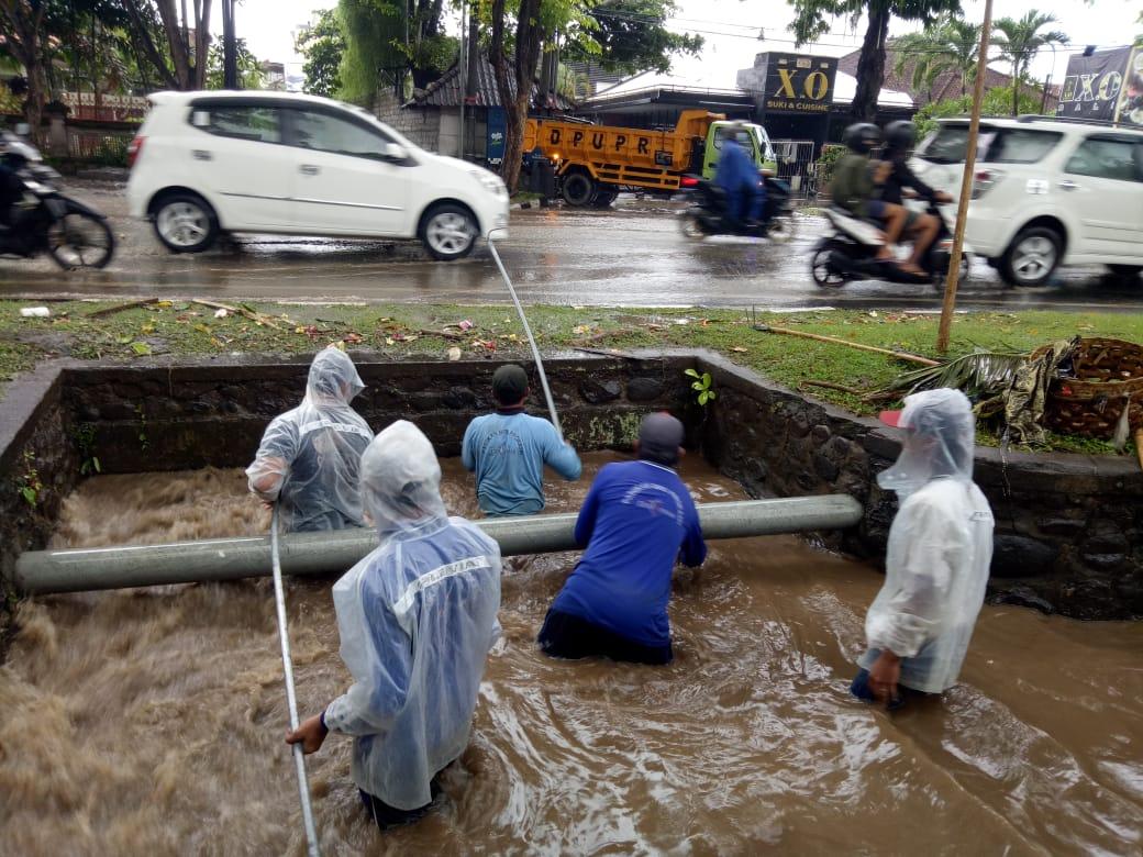 PETUGAS PUPR Kota Denpasar berjibaku menaikkan sampah yang menyumbat saluran drainase, Senin (14/12/2020). Foto: ist