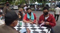 PETUGAS Satpol PP Klungkung memberi sanksi denda kepada warga yang melanggar prokes di Jalan Raya Goa Lawah, Kecamatan Dawan, Rabu (2/12/2020). Foto: ist