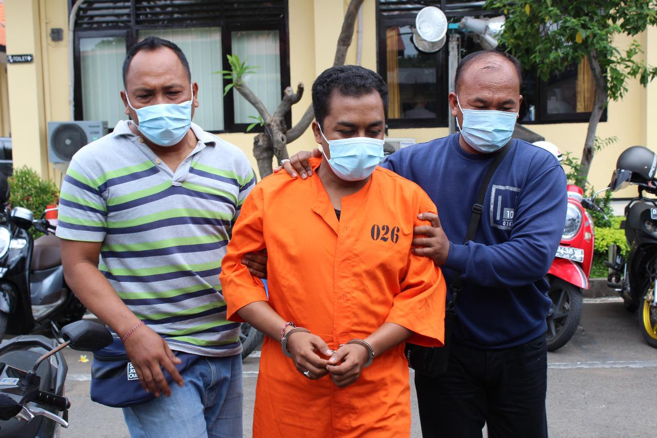 DEWA Swela, tersangka pencurian sejumlah perhiasan emas saat digiring anggota polisi di Mapolres Buleleng. Foto: rik
