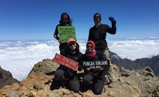 WISATAWAN berfoto usai mendaki puncak Gunung Rinjani di Pulau Lombok, Minggu (27/12/2020). Foto: rul