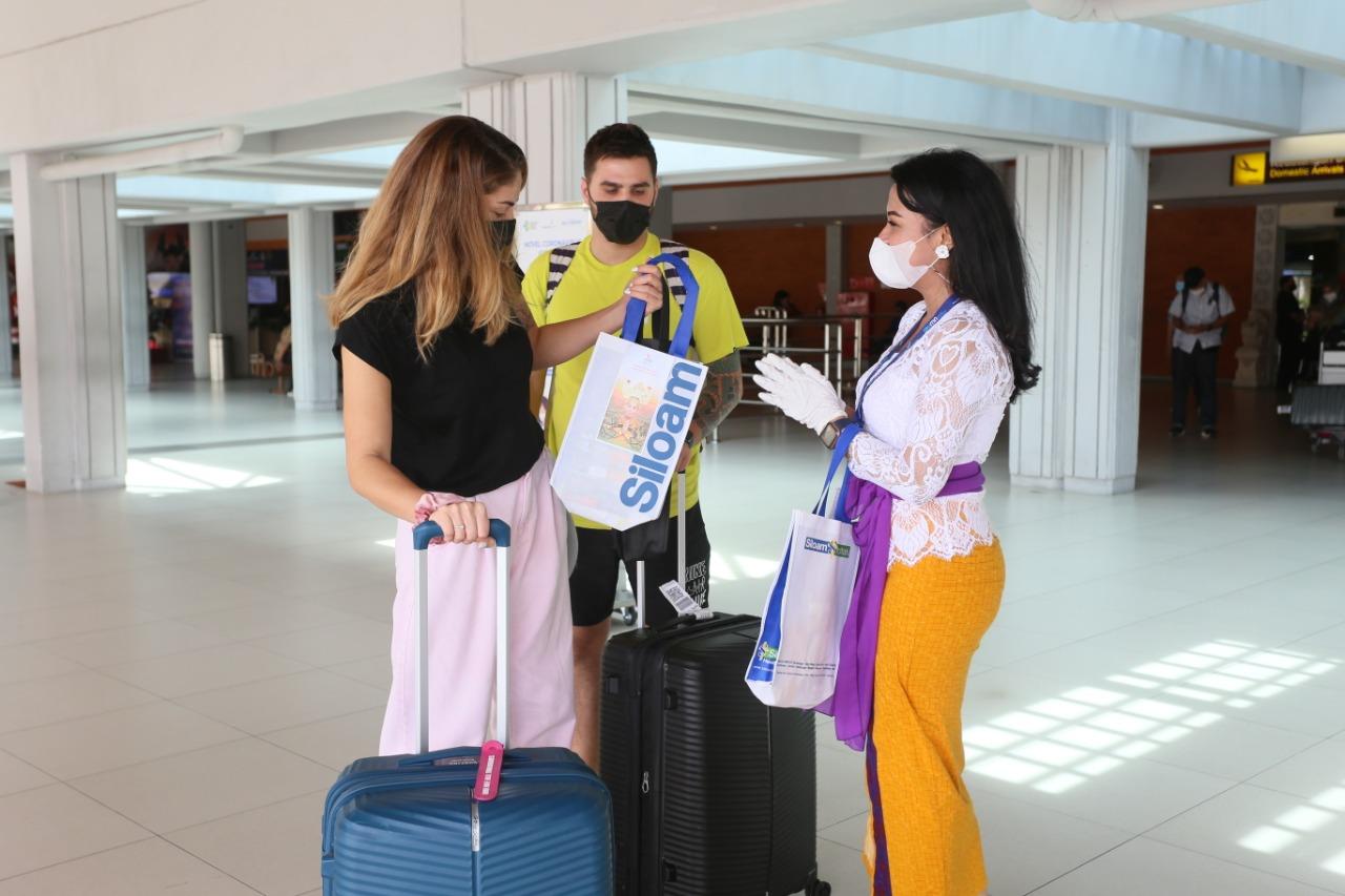 PETUGAS Bandara Ngurah Rai memberikan bingkisan kepada penumpang perempuan yang baru tiba di Bali, Selasa (22/12/2020). Foto: ist