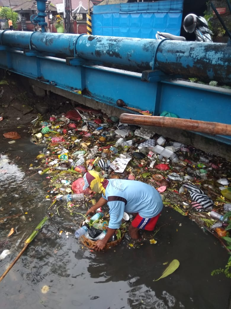 PETUGAS Pasukan Biru Prokasih DPUPR Kota Denpasar saat menaikkan sampah dari salah satu sungai, Senin (4/1/2021). Foto: ist