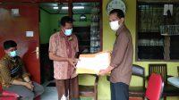 KADISDUKCAPIL Kota Denpasar, Dewa Gde Juli Artabrata (kanan), menyerahkan Akta Kematian Mia Trisetyani Wadu (23) kepada keluarga korban pada Selasa (26/1/2021). Foto: ist