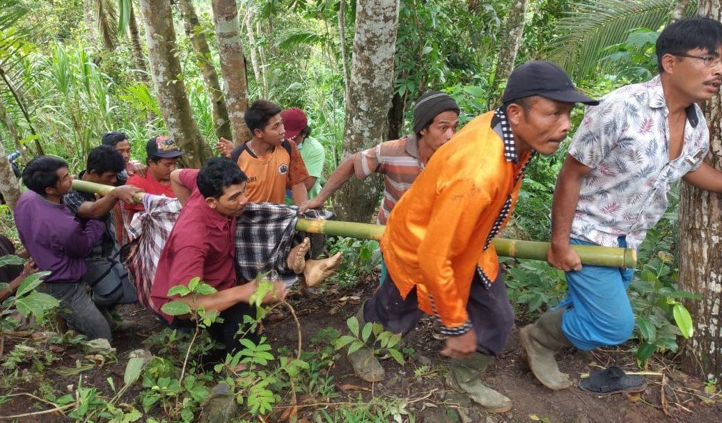 WARGA mengevakuasi jasad I Ketut Darma, warga Banjar Dinas Jumenang, Desa Bukit, Karangasem, Selasa (19/1/2021), yang tewas terkena pentalan kayu saat membantu merebah kayu durian. Foto: ist