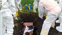 PETUGAS menurunkan peti jenazah pasien suspect virus Corona atau Covid-19 di Kuburan Batur utara. Foto: ist