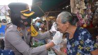 KAPOLRES Karangasem, AKBP Ni Nyoman Suartini, sedang memasangkan masker pada salah seorang pedagang di Pasar Desa Adat Ulakan, Kecamatan Manggis. Foto: ist
