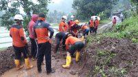 PETUGAS BPBD Buleleng dibantu warga desa Sepang Kelod, secara manual membersihkan material sisa longsor yang menutup jalan, yang dilakukan sebelum alat berat datang. Foto: ist