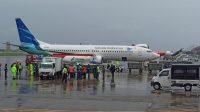 PROSES penurunan vaksin Covid-19 buatan Sinovac dari pesawat Garuda Indonesia yang mengangkutnya di base ops Lanud Ngurah Rai diiringi hujan lebat, Jumat (22/1/2021). Foto: ist