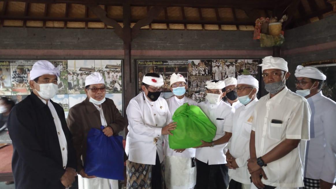 WAGUB Cok Ace menyerahkan bansos Surat Kabar Pos Bali di Pura Agung Besakih, Sabtu (9/1/2021). Foto: gay