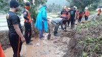 PETUGAS BPBD Buleleng dibantu warga Desa Sepang Kelod saat membersihkan sisa material longsor yang menutup jalan. Foto: rik