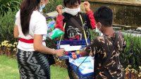 PEMUDA KNPI di Klungkung membagikan masker kepada anak penjual tisu di Monumen Puputan Klungkung. Foto: ist