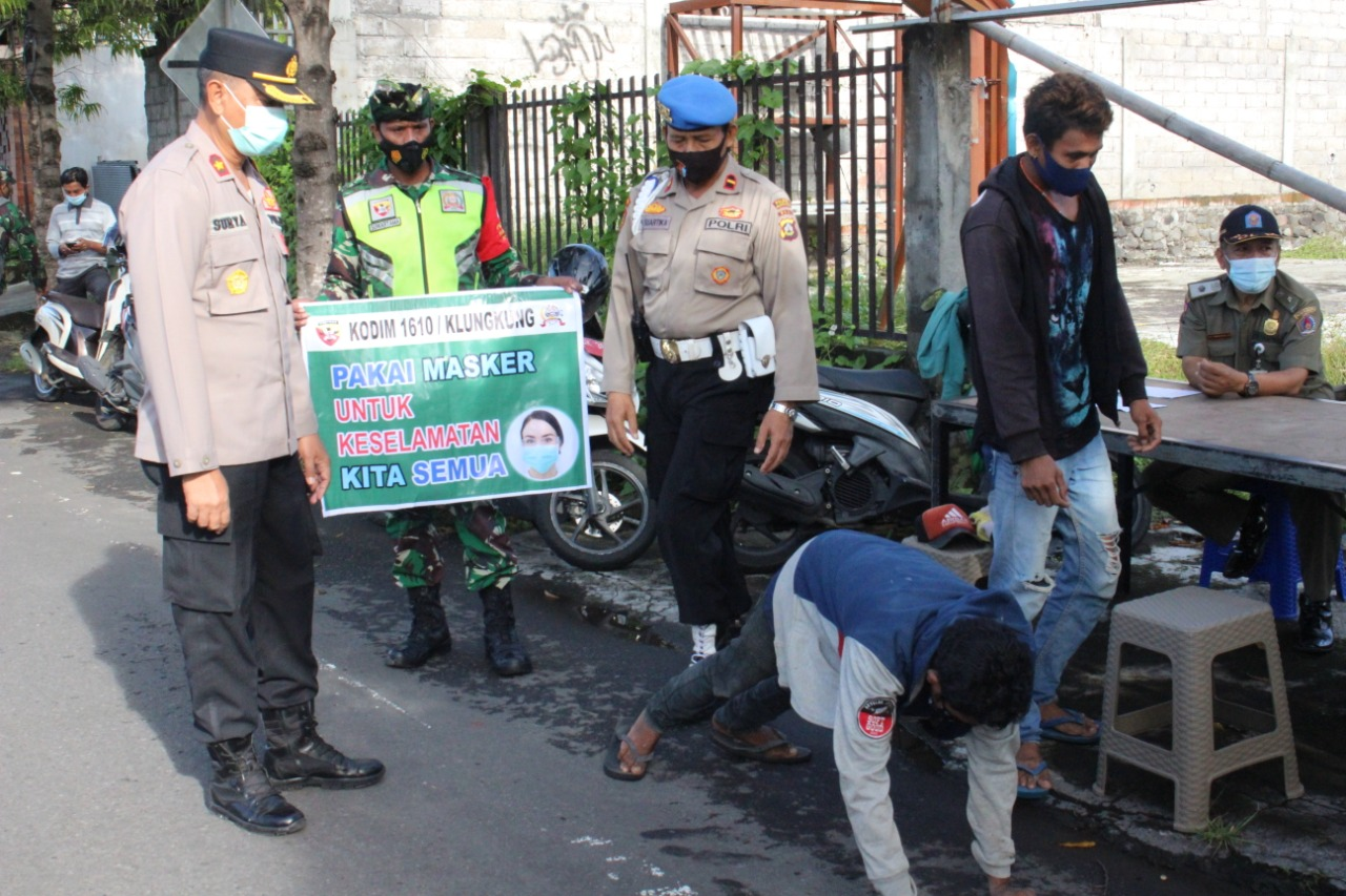 SEORANG warga menjalani hukuman push up setelah kedapatan tidak menggunakan masker dalam Operasi Yustisi di Jalan Rama, Kecamatan Klungkung, Kamis (4/2/2021). Foto: ist