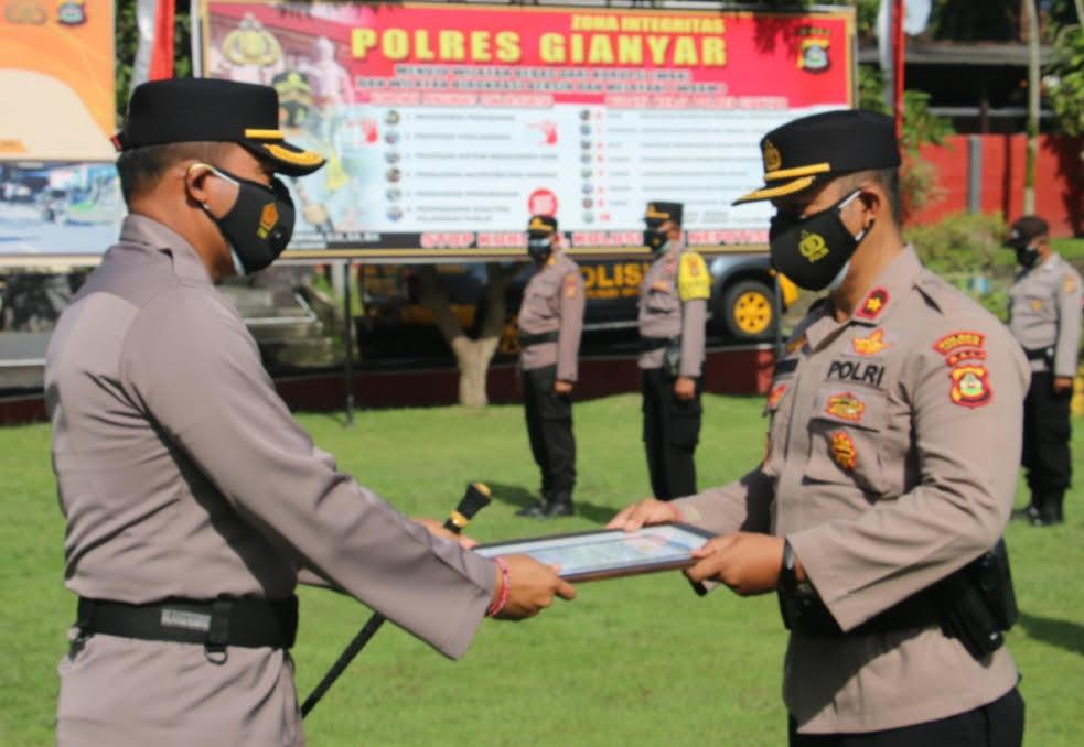 KAPOLRES Gianyar, AKBP I Dewa Made Adnyana, menyerahkan reward kepada personel berprestasi. Foto: adi