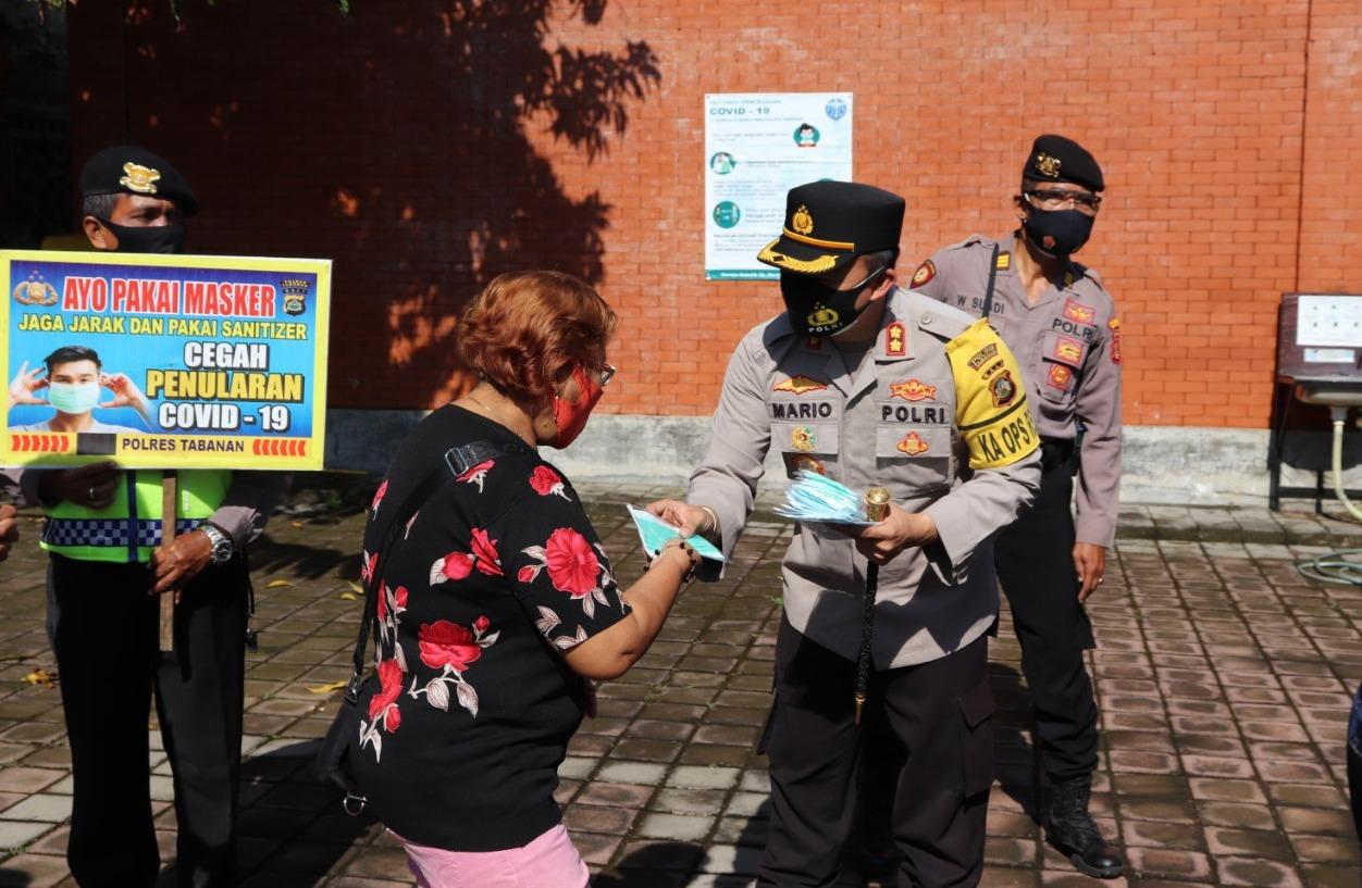 KAPOLRES Tabanan, AKBP Mariochristy Panca Sakti Siregar, bagi-bagi masker dan mengimbau disiplin prokes kepada jemaat Gereja St. Maria Immmaculata Tabanan, Minggu (7/2/2021). Foto: ist