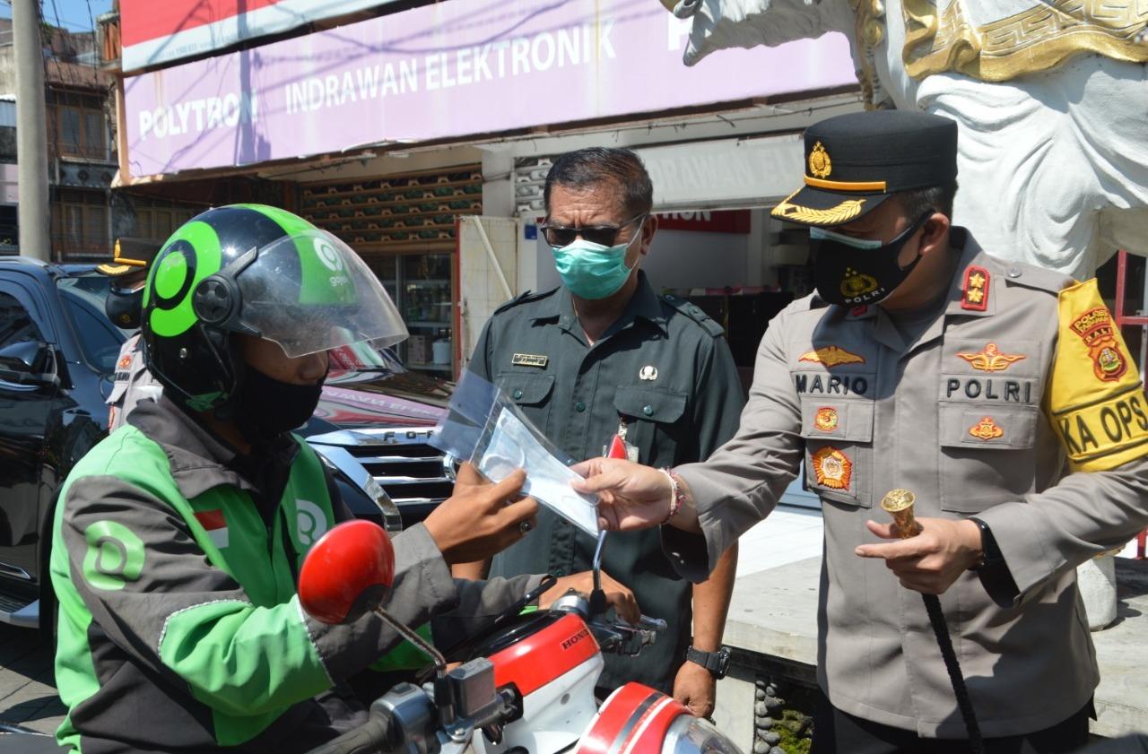 KAPOLRES Tabanan AKBP Mariochristy Panca Sakti Siregar melakukan langkah pencegahan penyebaran Covid-19 dengan membagikan masker kepada masyarakat, Selasa (2/2/2021). Foto: ist