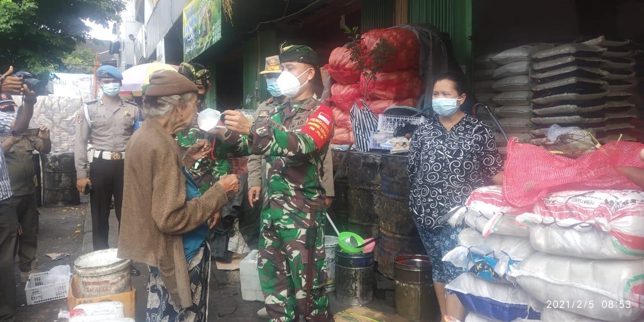 DANDIM 1623/Karangasem, Letkol Inf. Bima Santosa, mengenakan masker kepada salah satu pedagang saat Operasi Yustisi Prokes di Pasar Amlapura Timur, Kecamatan Karangasem, Jumat (5/2/2021). Foto: ist