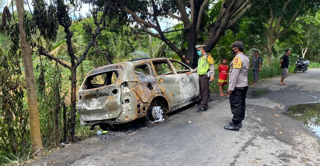 APARAT kepolisian di Nusa Penida melakukan olah TKP kebakaran mobil di Dusun Pelilit, Desa Pejukutan, Nusa Penida, Senin (15/2/2021) siang. Foto: ist
