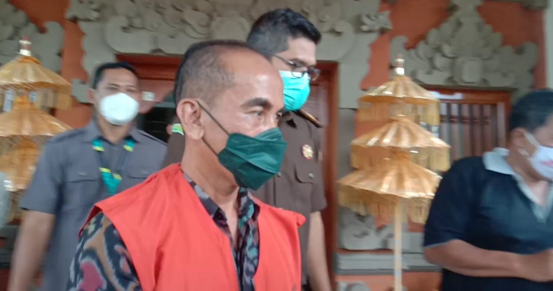 NYOMAN Gede Gunawan saat digiring menuju mobil tahanan di kantor Kejari Buleleng, Selasa (23/2/2021). Foto: ist