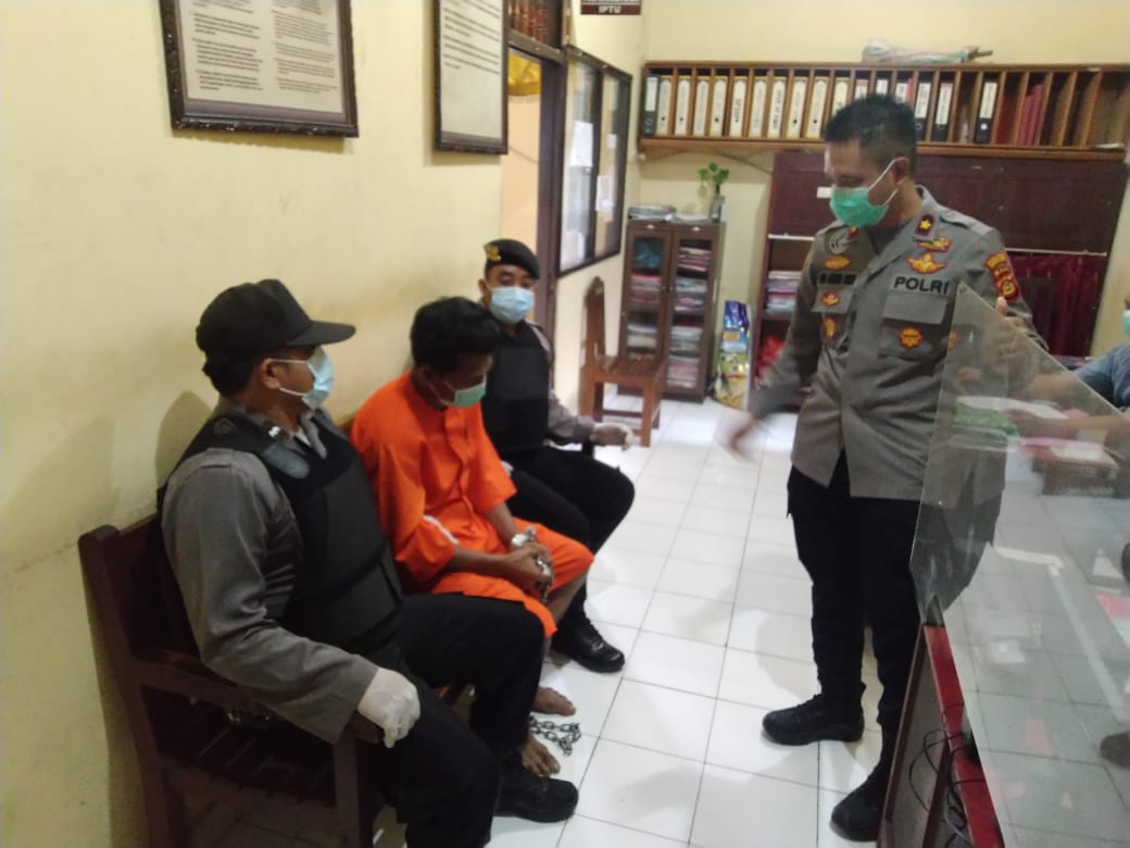 TERSANGKA Suarsana duduk sambil nunduk memakai baju tahanan saat berada di Mapolsek Banjar, Selasa (9/2/2021). Foto: ist