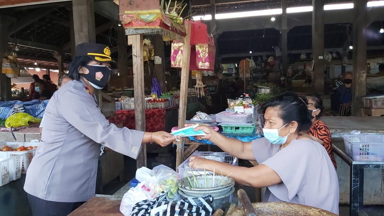 WAKAPOLRES Klungkung, Kompol Luh Ketut Amy Ramayathi Prakasa, membagikan masker ke pedagang di Pasar Tusan, Banjarangkan, Kamis (18/2/2021). Foto: ist