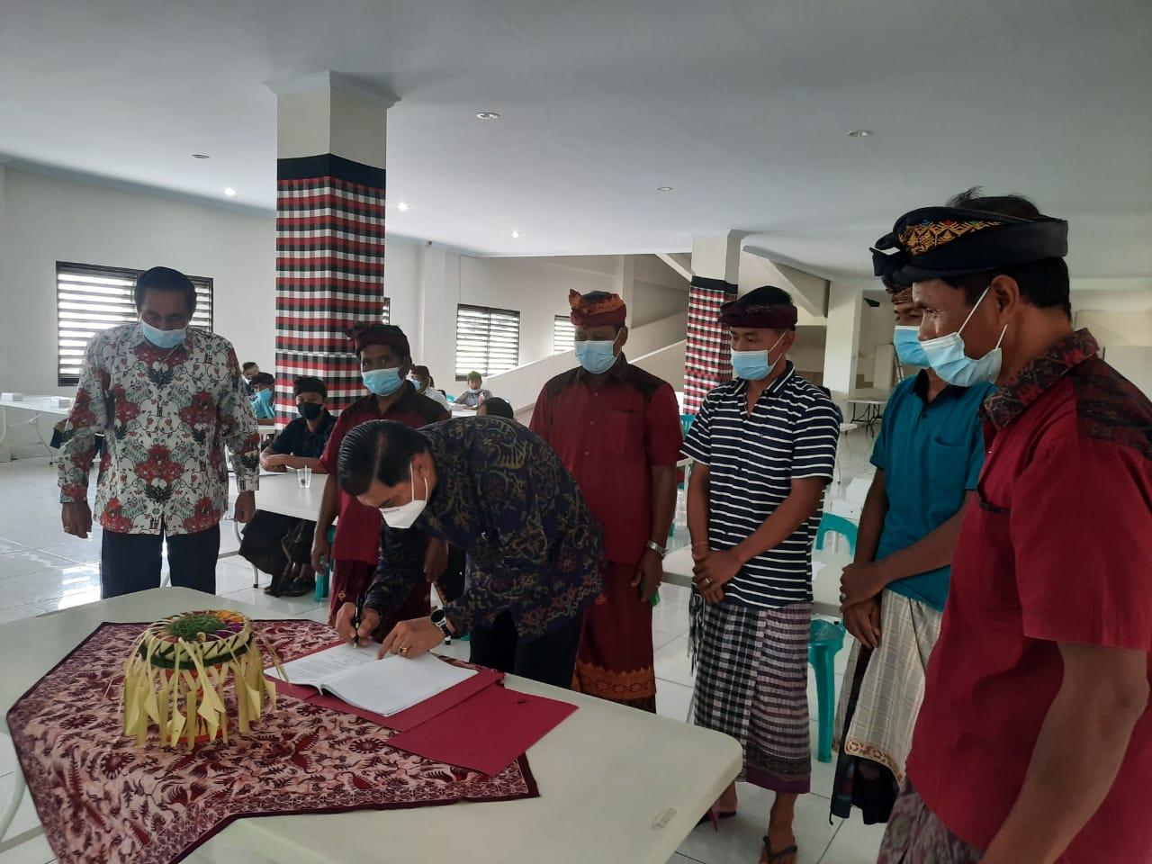KADISKOP UKM Badung, Made Widiana, menandatangani laporan pertanggung jawaban Koperasi Pandawa saat RAT. Foto: ist