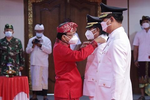 GUBERNUR Koster meletakkan tanda jabatan di pundak Giri Prasta sebagai Bupati Badung saat pelantikan di Wiswa Sabha Utama kantor Gubernur Bali, Jumat (26/2/2021). Gubernur mengingatkan berwenang sebagai wakil pemerintah pusat untuk memberi sanksi dan penghargaan kepada bupati/wali kota. Foto: ist