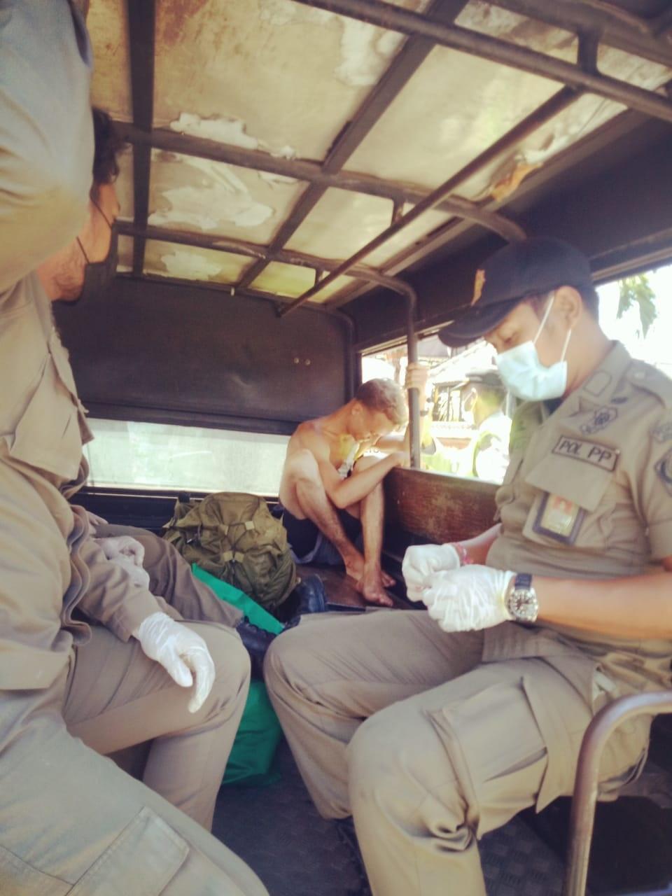 PETUGAS Satpol PP Kota Denpasar saat mengangkut bule yang mengamuk di Sanur, Senin (29/3/2021). Foto: ist
