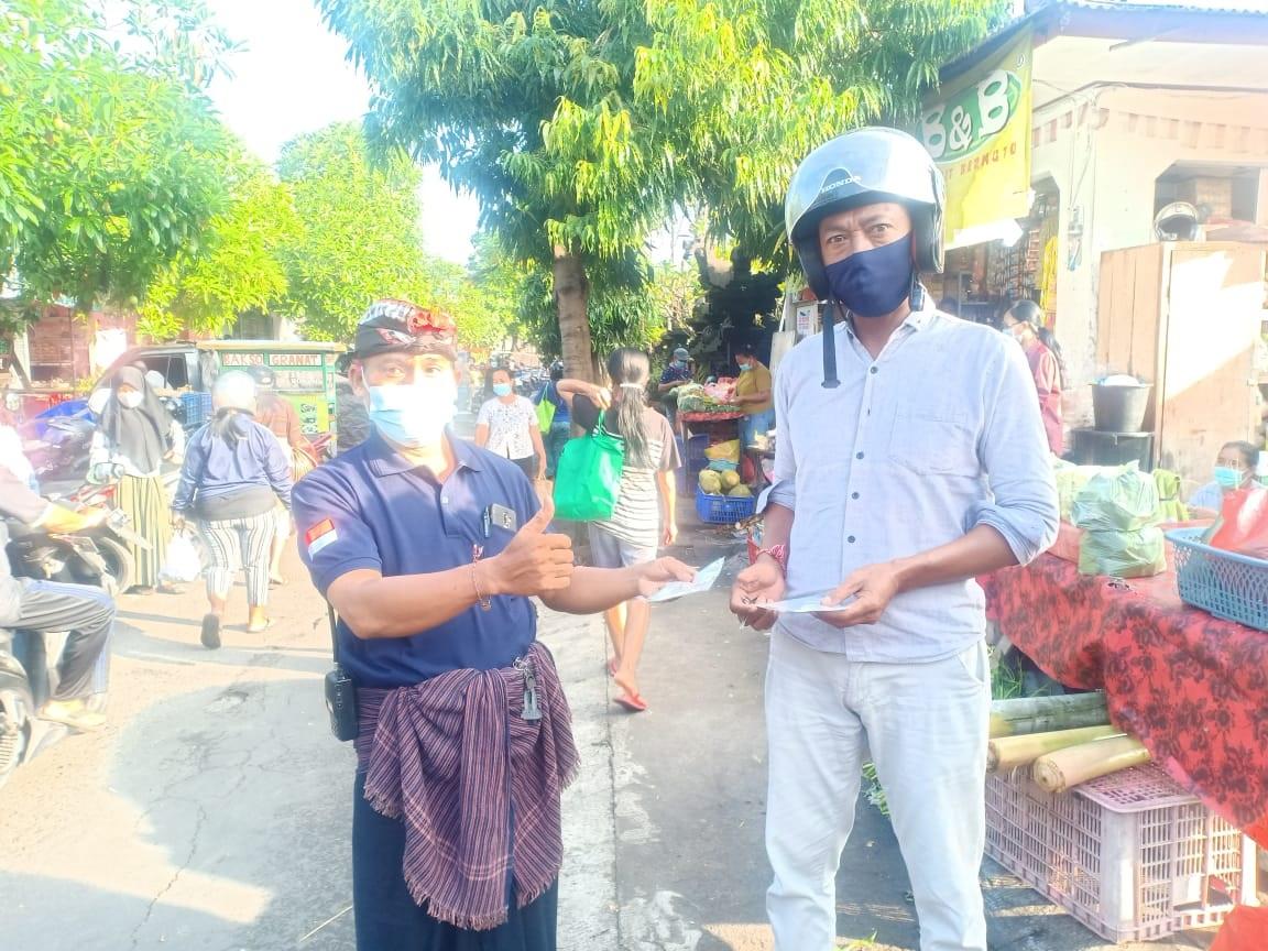 PEMBERIAN masker secara gratis kepada pembeli dan pedagang di Pasar Ketapian, Kelurahan Sumerta, Kota Denpasar. Foto: ist