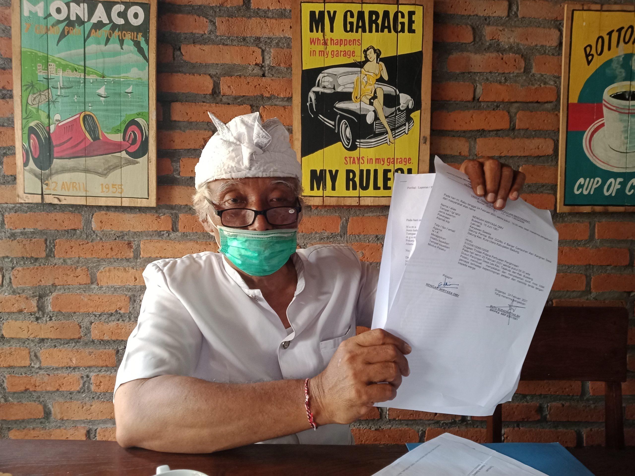 KELIAN Desa Adat Les Penuktukan, Jro Pasek Nengah Wiryasa, menunjukkan laporan polisi. Foto: rik