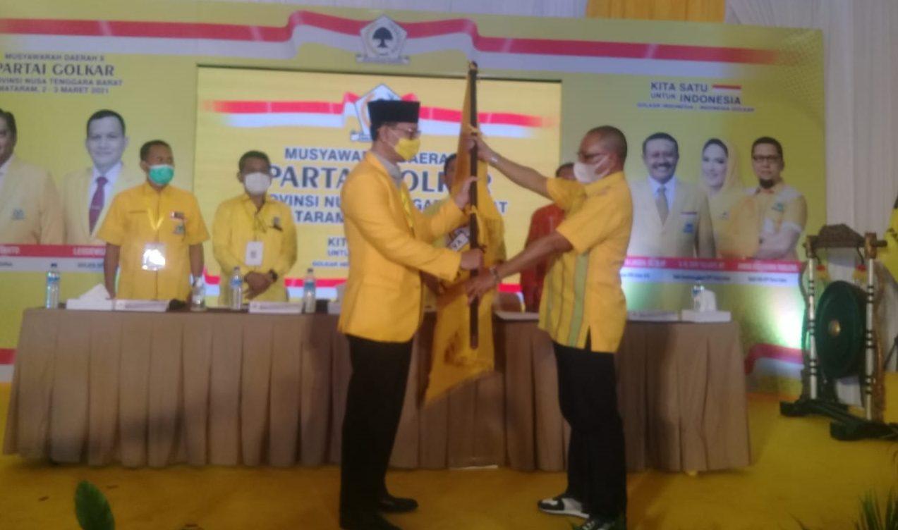 WAKIL Sekjen DPP Partai Golkar yang juga pimpinan pleno Musda X dari perwakilan DPP Golkar, Hermanus Bele Hayong, menyerahkan bendera Partai Golkar kepada Mohan Roliskana yang disahkan sebagai Ketua Golkar NTB, Rabu (3/3/2021). Foto: rul