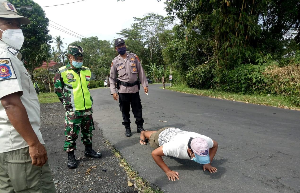 TIM Satgas Penanganan Covid-19 Kabupaten Bangli memberikan sanksi push up guna memberi efek jera kepada pelanggar prokes. Foto: ist