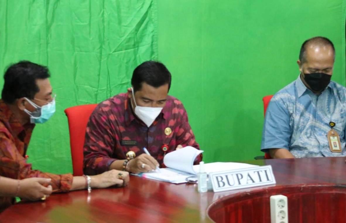 BUPATI Tabanan, I Komang Gede Sanjaya, saat menandatangani perjanjian kerja sama tahap III Optimalisasi Pemungutan Pajak Pusat dan Pajak Daerah, antara DJP, DJPK, dan pemda, Rabu (21/4/2021). Foto: ist
