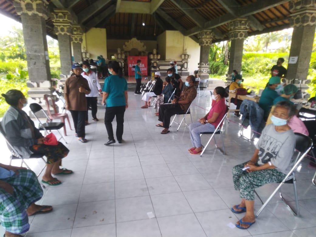 PULUHAN lansia antusias berdatangan diantarkan anggota keluarga untuk mengikuti vaksinasi Covid-19 di wantilan kantor Camat Selat, Kamis (8/4/2021). Foto: nad