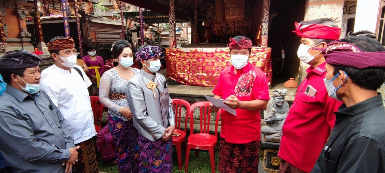 BUPATI Bangli, Sang Nyoman Sedana Arta, menyerahkan akta pernikahan, KTP dan KK atas nama I Wayan Suwendra dengan Ni Wayan Sintia di Br. Tiga, Desa Tiga, Susut, Sabtu (5/6/2021). Foto: ist