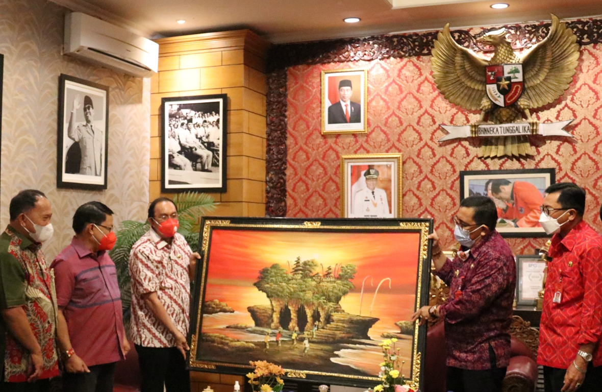 BUPATI Tabanan, I Komang Gede Sanjaya, saat memberikan cenderamata berupa lukisan alam Tanah Lot, kepada Bupati Minahasa, Royke Octavian Roring, di Ruang Kerja Bupati Tabanan, Senin (21/6/2021). Foto: ist