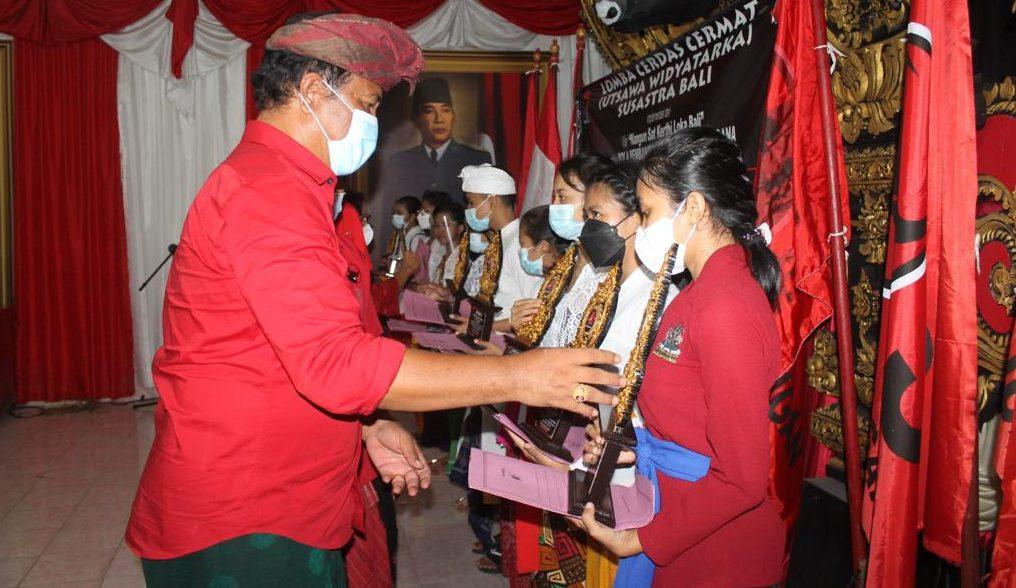 KETUA DPC PDIP Klungkung, AA Gde Anom, menyerahkan hadiah kepada pemenang lomba cerdas cermat susastra Bali di sekretariat DPC PDIP Klungkung, Sabtu (5/6/2021). Foto: ist