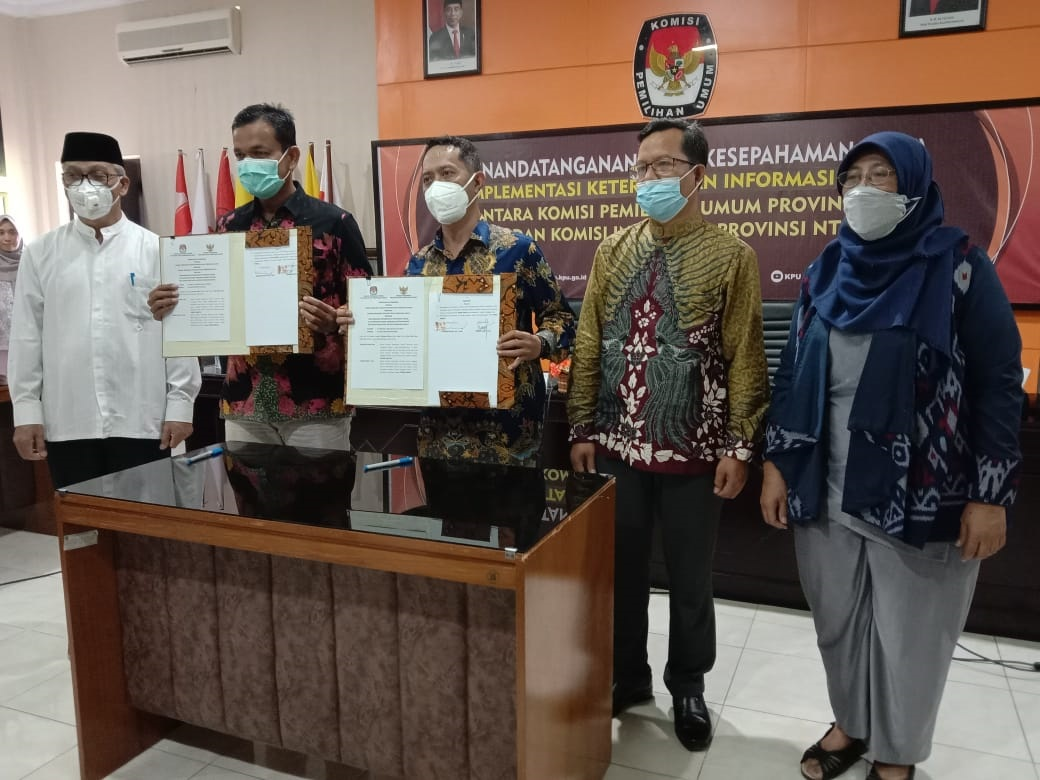 KETUA KPU NTB, Suhardi Soud (dua kiri), bersama Ketua KI NTB, Sueb Qury (tengah), menunjukkan nota kesepahaman Implementasi Keterbukaan Informasi Publik (KIP) di lingkup KPU se-NTB, Jumat (18/6/2021). Foto: rul