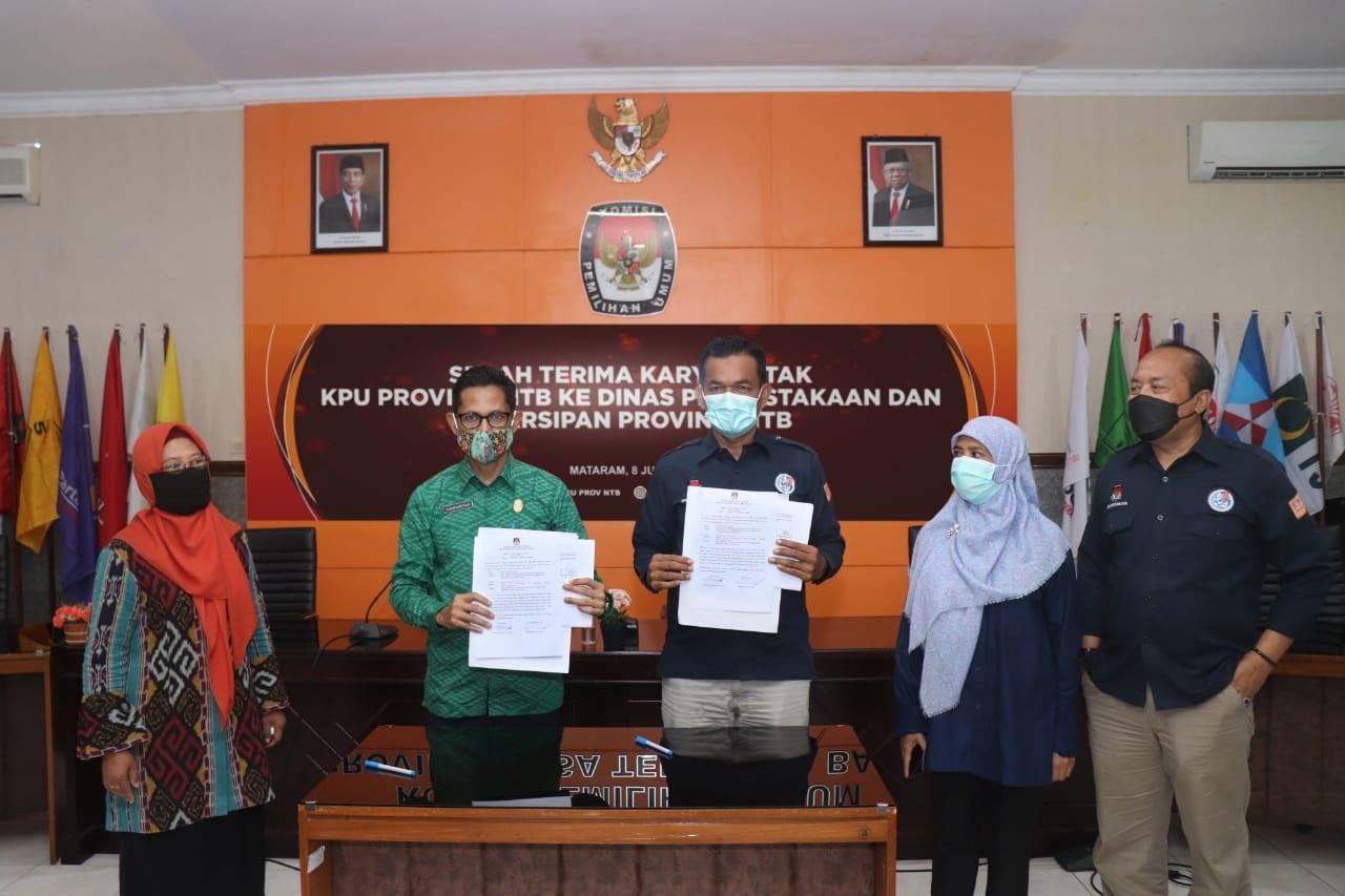 KETUA KPU NTB, Suhardi Soud (tiga kanan), menunjukkan dokumen serah-terima dokumen penyelenggaraan demokrasi NTB kepada Kepala Dinas Perpustakaan dan Kearsipan, Julmansyah (dua kiri), Selasa (8/6/2021). Foto: ist