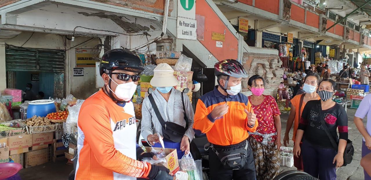 LIDARTAWAN bersama Rentin dan komisioner lainnya saat membagikan masker di Pasar Kereneng, Denpasar usai gowes dari daerah Sangeh di Kabupaten Badung, Jumat (4/6/2021). Foto: hen