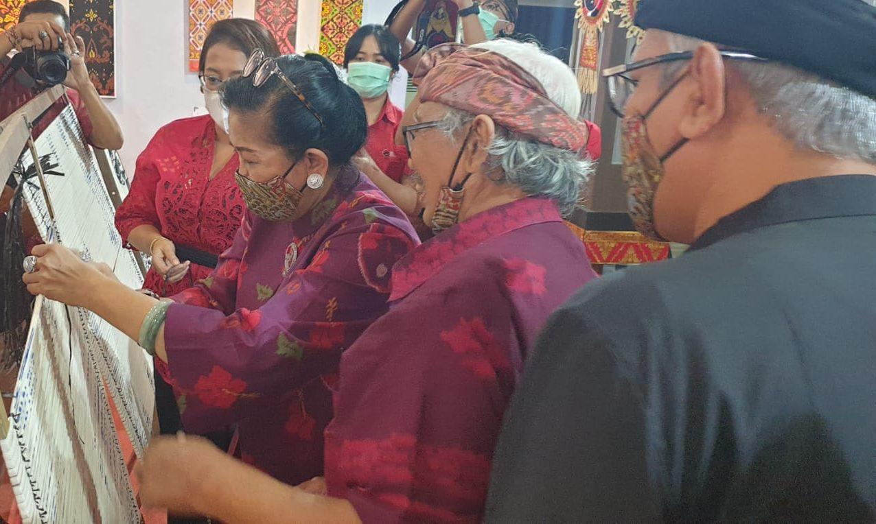 PUTRI Suastini Koster didampingi perajin Nyoman Sudira mencoba membuat motif tenun ikat saat workshop Kreativitas Mendesain Endek Bali dengan Teknik Digital dan Harmoni Pewarnaan yang dilangsungkan DPD PDIP Bali, Minggu (6/6/2021). Foto: hen
